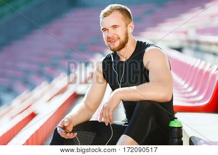 Man taking stop after running on track, looking ahead. Sportsman in black training suit sitting on tribune of stadium. Outdoors, stadium, sunlight, unfocused background