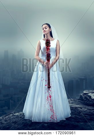 Bride in white wedding dress with bloody bat