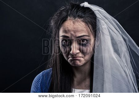 Bride with tear-stained face on black background