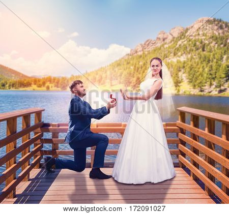 Groom makes a proposal of marriage on the pier
