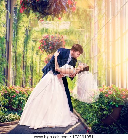 Beautiful newlyweds embrace in a green garden