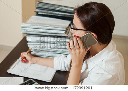 Female bookkeeper in glasses talking by phone