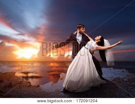 Newlyweds dancing, sea and sunset on background