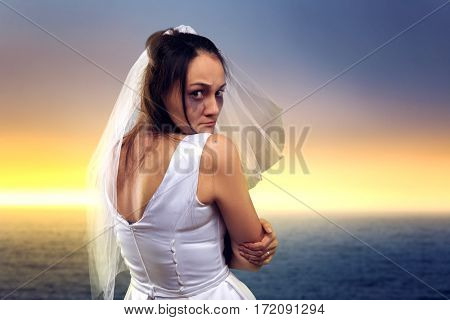 Bride on the background of the sea and sunset
