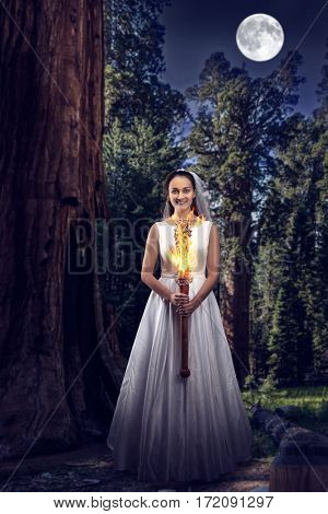 Bride with the burning torch in the night wood