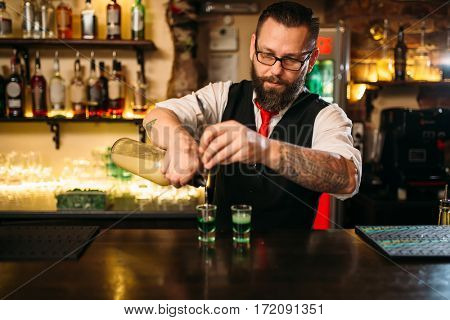 Barkeeper pouring alcoholic beverage in glass