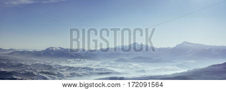 Snowy mountains peaks with mist at sunny day. Carpathian, Ukraine, Europe.