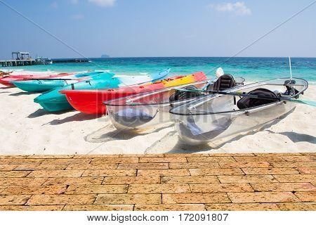 kayaks on the tropical beach with brick wall