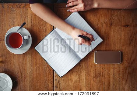 Top view of female hands writing in notebook
