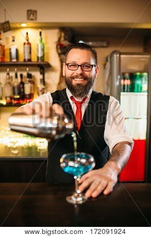 Bartender with shaker making alcohol cocktail