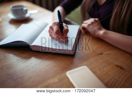 Female hands writing in notebook closeup