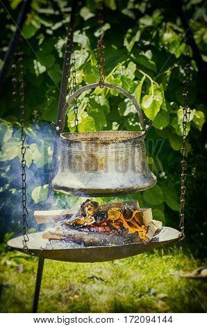 Vintage Metallic Pot Under Fire Over Natural Background