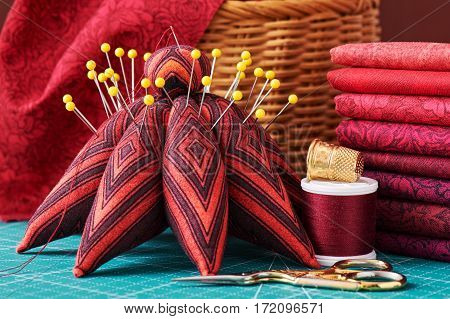 Set of red fabric and sewing tools on craft mat close-up view
