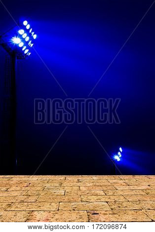 Stadium floodlights on a sports field at night with brick wall