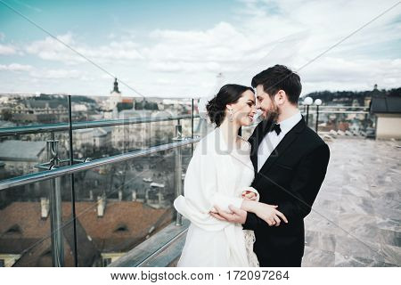 Nice brunette bride and bridegroom standing close to each other at old city background and smiling, wedding photo.