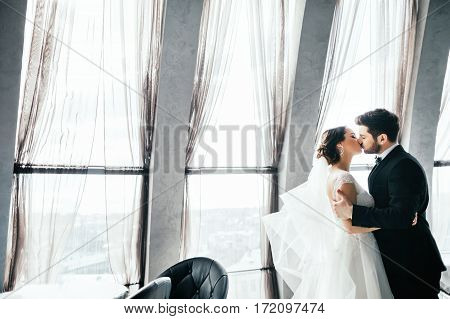 Beautiful brunette bride and bridegroom standing close to each other and kissing at big window at background, wedding photo.