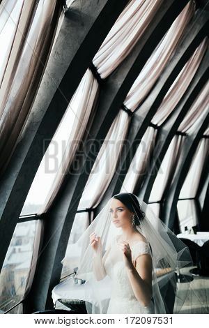 Beautiful bride with dark hair wearing white wedding dress standing near big window and looking up, portrait.