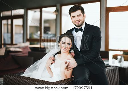Beautiful bride and bridegroom sitting at big window at background and smiling, wedding photo, portrait.