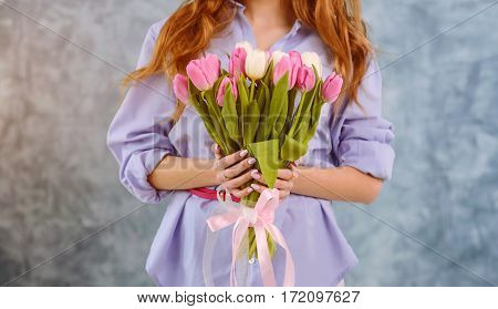 Two hands with bouquet of tulips on the blue wall background