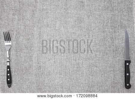 Tablecloth from rough linen fabric with a fork and knife. Creative background for banner or menu cafe or restaurant
