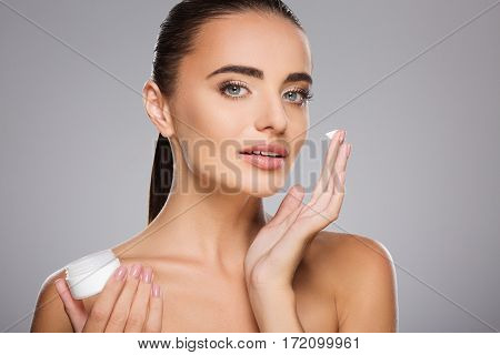 Beautiful girl with brown hair fixed behind, clean fresh skin, big eyes and naked shoulders holding a drop of cream, posing at gray studio background, face care.
