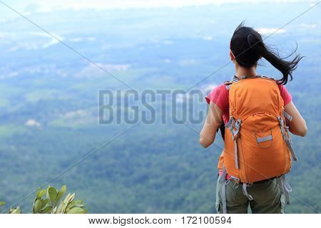 young traveler with backpack standing on the mountain peak
