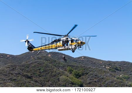 Los Angeles County Fire Department helicopter hoisting a paramedic. Taken 09/18/2016 in Newton Canyon off Kanan Rd. in Malibu CA.