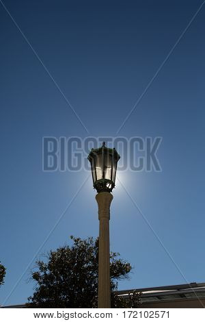 Old gas lamp back lit by the sun against a blue sky