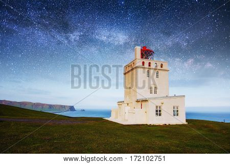 Fantastic starry sky and the milky way. Dramatic and picturesque scene. Beautiful white lighthouse at Cape Dyrholaey, South Iceland.