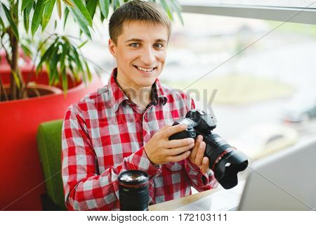 Smiling young man sitting in cafe with laptop and professional camera, working with computer, internet and camera, portrait.