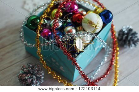 Paper box filled with colorful Christmas decorations, isolated on a white wooden background. In anticipation of the holiday.