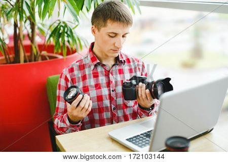 Handsome young man sitting in cafe with laptop and choosing professional camera, photographer, portrait, copy space.