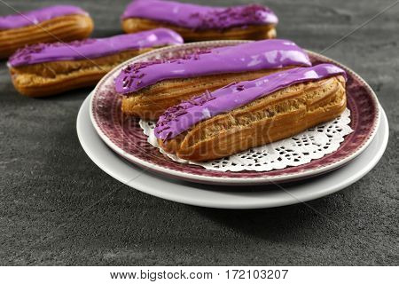 Plate with delicious glazed eclairs on dark textured background