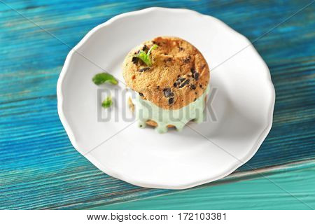 Plate with delicious kiwi ice cream cookie sandwich on wooden board