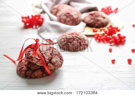 Delicious chocolate cookies and viburnum on white wooden table, closeup