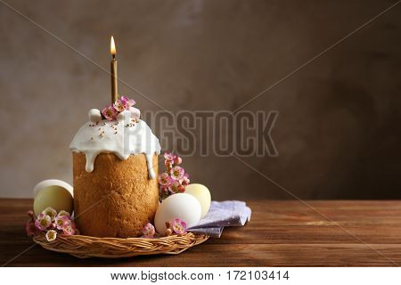Wicker plate with Easter cake, lighted candle and painted eggs on wooden table