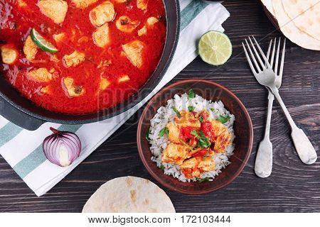 Chicken tikka masala in pan and portion with rice on wooden table