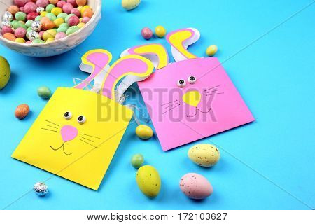 Easter concept. Funny bags and colourful candies on blue background