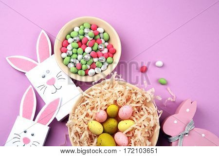 Easter concept. Paper bags with colourful eggs and candies on purple background