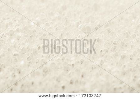 Close-up texture fragment of a white sponge as a backdrop composition with a shallow depth of field