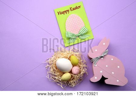 Easter concept. Greeting card and colourful eggs in decorative nest on purple background