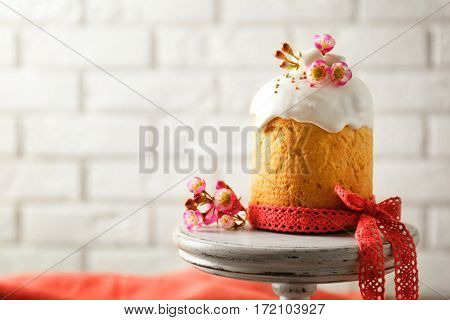 Dessert stand with sweet Easter cake on brick wall background