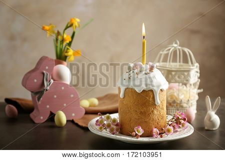 Easter cake with lighted candle on table