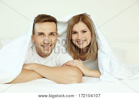 Young cute couple in bed under sheet