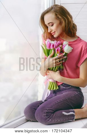 Pretty young woman in pink T-shirt with bouquet of tulips on window-sill