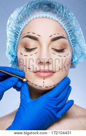 Gorgeous girl with dark eyebrows wearing blue medical hat at studio background, doctor's hand making perforation lines on patient's face.