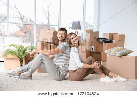 Happy family couple with cardboard boxes at home