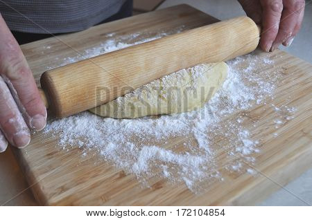 Caucasian male hands rolling a filled out dough filled with pastry filling, close-up