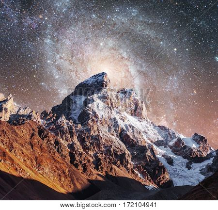Fantastic starry sky. Courtesy of NASA. Autumn landscape and snow-capped peaks. Main Caucasian Ridge. Mountain View from Mount Ushba Meyer, Georgia. Europe.