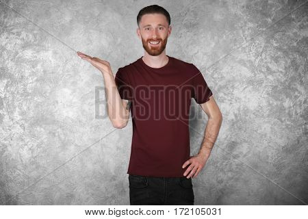 Young handsome man in claret red T-shirt on colour textured wall background